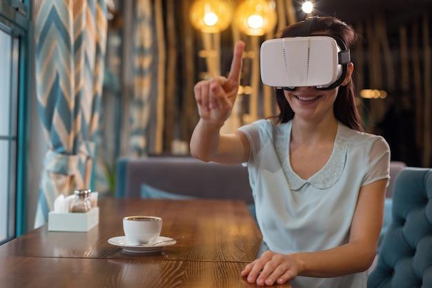 Świat vr. dobrze wyglądająca, wesoła atrakcyjna kobieta, podnosząc rękę, uśmiechając się i używając okularów vr