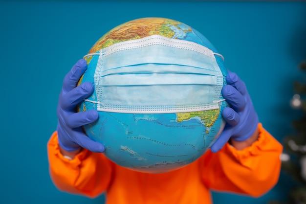 Świat z maską medyczną w rękach