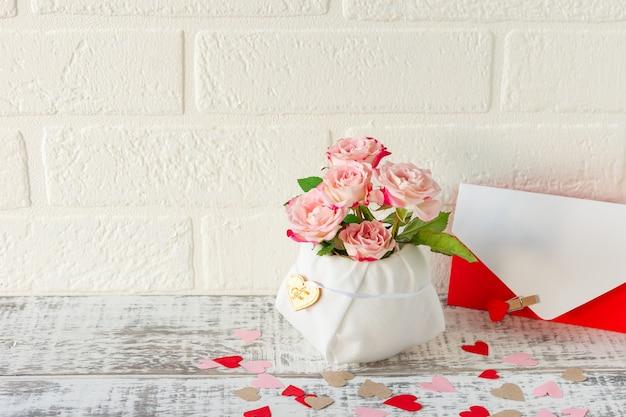 Świąteczna aranżacja bukietu róż i koperty z listem z życzeniami na wakacje.