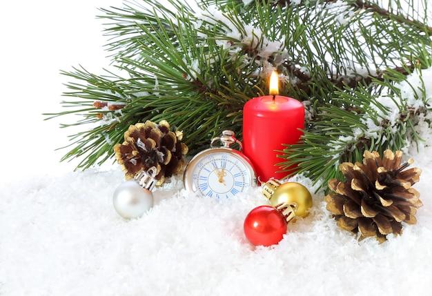 Świąteczna aranżacja z zegarkami kieszonkowymi i płonącą świecą na białym tle