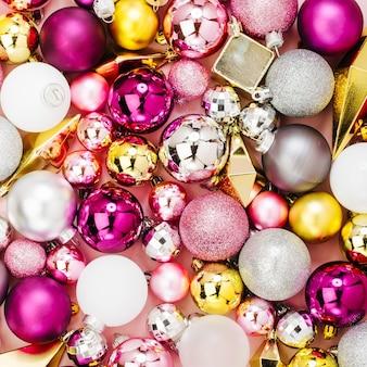 Świąteczna aranżacja ze stylowymi świątecznymi błyszczącymi bombkami i złotymi kryształkami na pastelowym różowym tle. płaski układanie, widok z góry