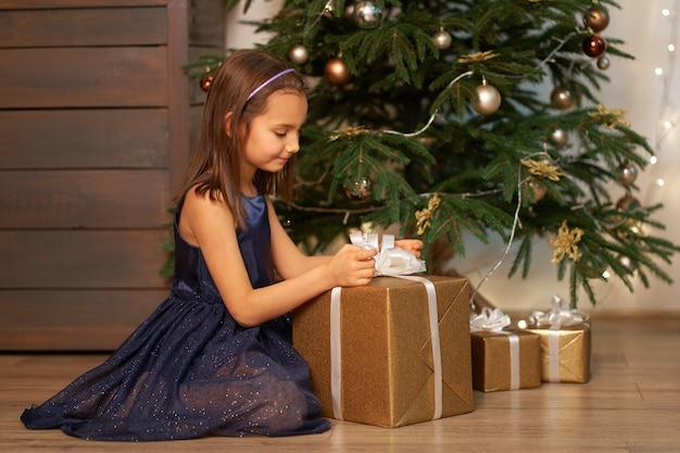 Świąteczna bajka magiczna. mała dziewczynka marzy przed otwarciem prezentu od mikołaja na boże narodzenie