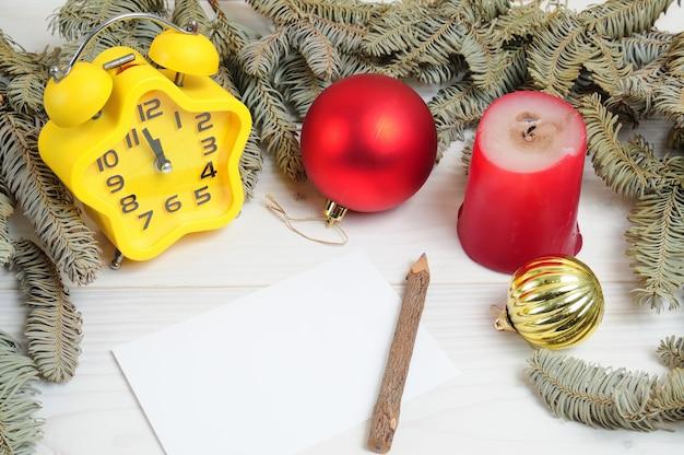 Świąteczna biała drewniana wzorzysta powierzchnia z gałązkami choinki, zabawkami, zegarem i białym papierem