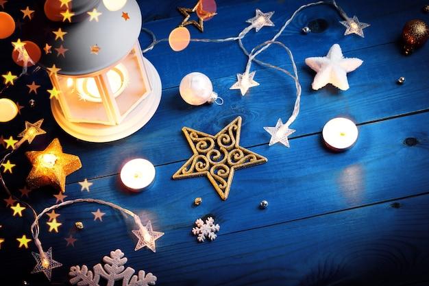 Świąteczna biała latarnia ze świecami i dekoracjami na niebieskiej powierzchni drewnianej