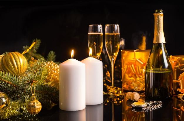 Świąteczna bożonarodzeniowa martwa natura z szampanem w butelce i fletach, płonące białe świece i złote prezenty i bombki na ciemnym tle