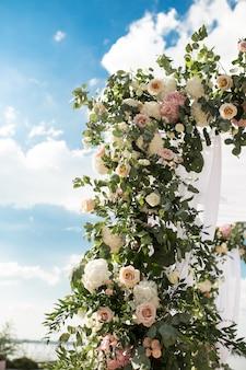Świąteczna chuppa ozdobiona świeżymi pięknymi kwiatami na ślub na świeżym powietrzu.