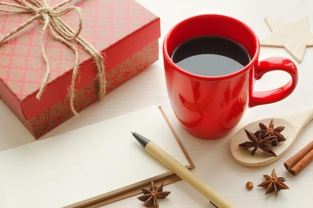 Świąteczna czerwona filiżanka czarnej mocnej kawy z przyprawami, piękne pudełko prezentowe, pusty notes i długopis