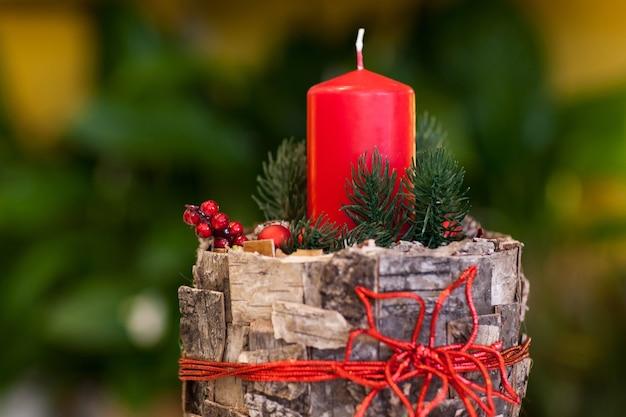 Świąteczna czerwona świeca na pniu ozdobiona korą drzewa oraz jagodami i gałązkami jodły