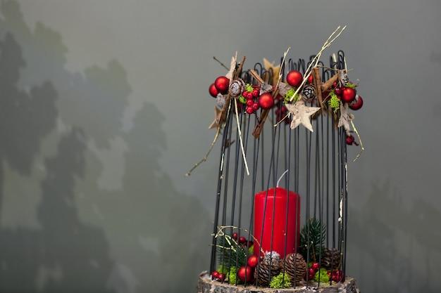 Świąteczna czerwona świeca na pniu ozdobiona metalowymi prętami i szyszkami jodły na szarym tle