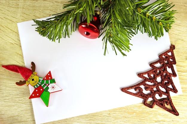 Świąteczna dekoracja 2021 z świątecznymi gałęziami, zabawkami i dzwonkiem. ozdoby świąteczne i zabawki. list do świętego mikołaja. noworoczna atmosfera.