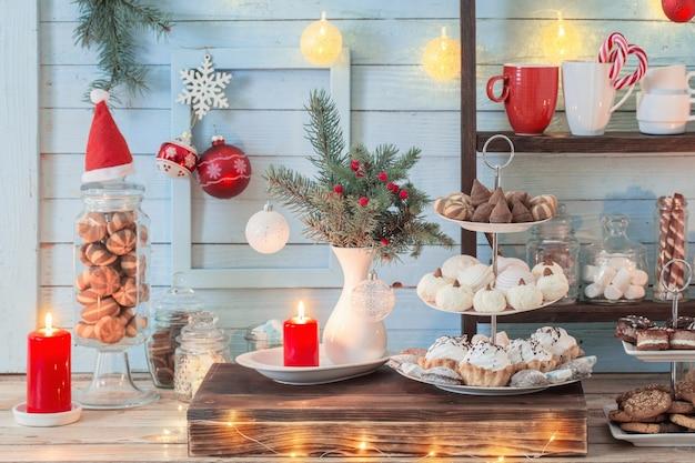 Świąteczna dekoracja bar kakaowa z ciastkami i słodyczami na niebieskim tle drewnianych w stylu vintage