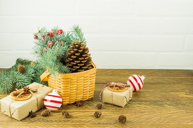 Świąteczna dekoracja domu na boże narodzenie. wiklinowy kosz z gałęzi świerkowych i jagód, szyszka cedrowego i pudełka na drewnianym stole.