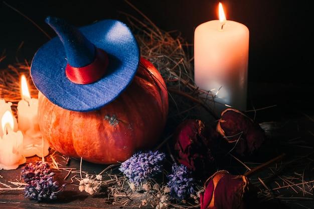 Świąteczna dekoracja halloween z pomarańczową dynią z kapeluszem czarownicy, świecami, różami i suchym sianem.
