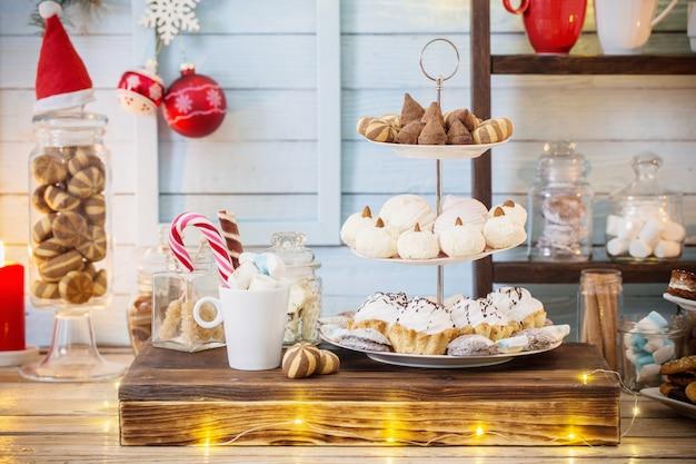 Świąteczna dekoracja kakao z ciasteczkami i słodyczami na niebieskim drewnianym tle w stylu vintage