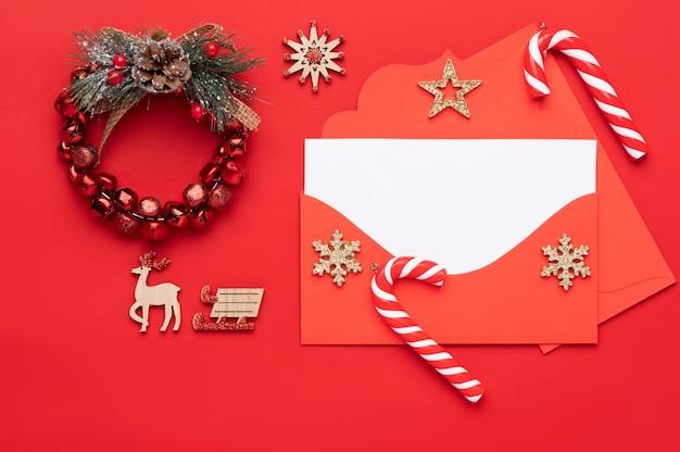 Świąteczna dekoracja na czerwonym tle, składająca się z czerwonej koperty z pustym białym nagłówkiem na tekst i ozdobiona świątecznymi cukierkami i wieńcem noworocznym
