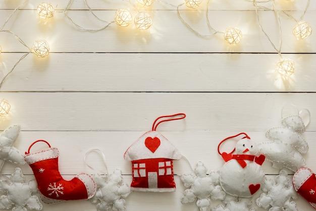 Świąteczna dekoracja na drewnianym tle. płaskie legowisko z ręcznie robionym domkiem, bałwanem, płatkami śniegu w kolorze białym