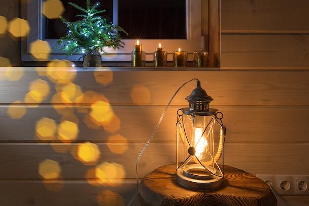 Świąteczna dekoracja okienna z czterema złotymi świecami i latarnią na tle w drewnianym domu. świeczki adwentowe i mała choinka.
