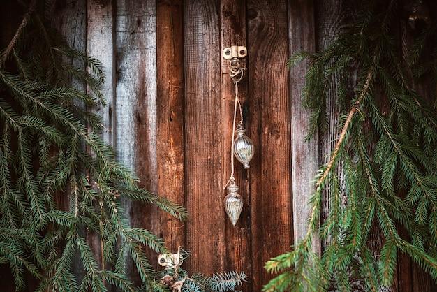 Świąteczna dekoracja okna z gałązkami jodły, girlandami i szyszkami. wesołych świąt bożego narodzenia znak i bombki na parapecie