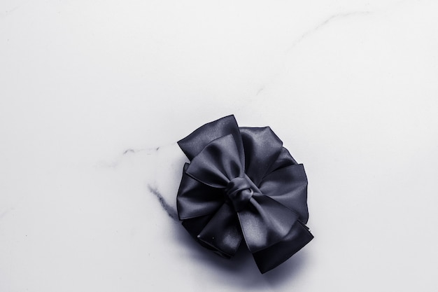 Świąteczna dekoracja prezentów i koncepcja promocji sprzedaży czarna jedwabna wstążka i kokardka na marmurowym tle f...