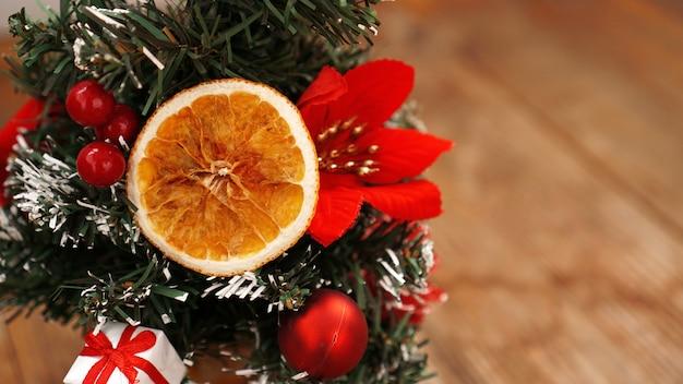 Świąteczna dekoracja przeciw drewnianemu niewyraźnemu tłu z choinką, suszonymi owocami