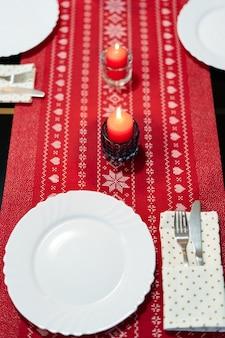 Świąteczna dekoracja stołu na święta nowego roku z czerwonymi świecami i białymi talerzami na czerwonym obrusie