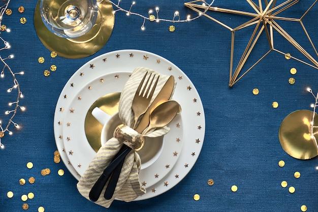 Świąteczna dekoracja stołu z białym talerzem i złotymi naczyniami oraz złoconymi dekoracjami.
