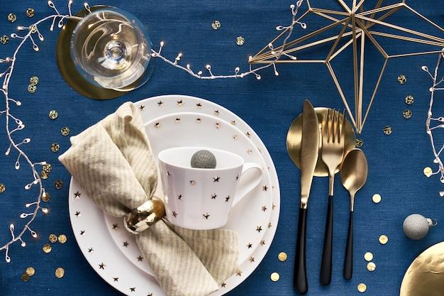 Świąteczna dekoracja stołu z białym talerzem, złotymi naczyniami i pozłacanym geometrycznym metalowym drutem