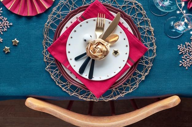 Świąteczna dekoracja stołu z białymi talerzami, złotymi naczyniami i ciemnoczerwonymi złoconymi dekoracjami