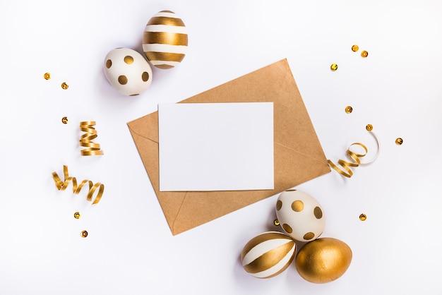 Świąteczna dekoracja wielkanocna. widok z góry na pisanki i pustą kartę w kopercie siarczanowej.