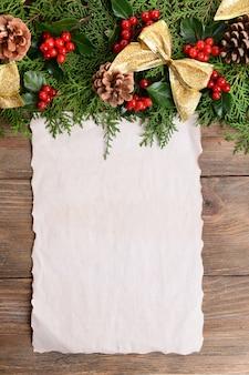 Świąteczna dekoracja z arkuszem papieru na drewnianym tle