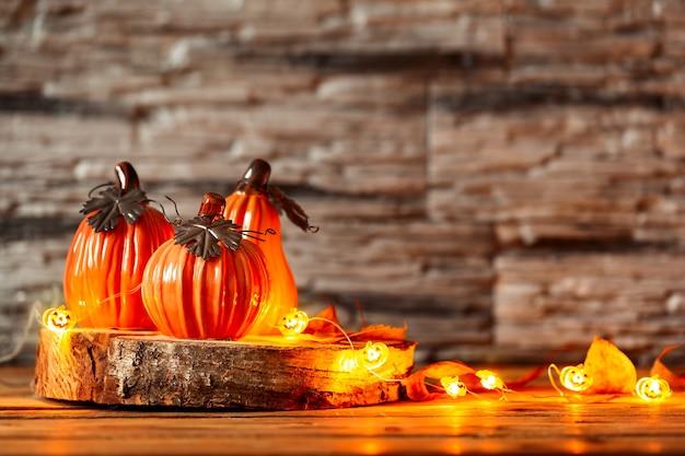 Świąteczna dekoracja z dekoracyjnymi ceramicznymi dyniami z dekoracją świetlna girlanda świecąca na drewnianym stole. halloweenowy tło.