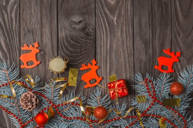 Świąteczna dekoracja z gałązkami jodły i czerwonymi bombkami na ciemnym drewnianym tle