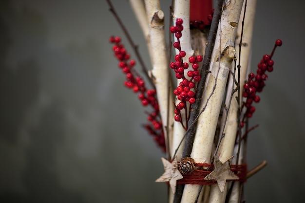Świąteczna dekoracja z wiązek drewnianych gałęzi z jagodami i szyszkami jodły na szarym tle