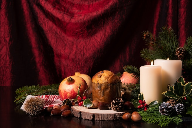 Świąteczna dekoracja ze świecami, szyszki, gałązka sosny, owoce i panettone