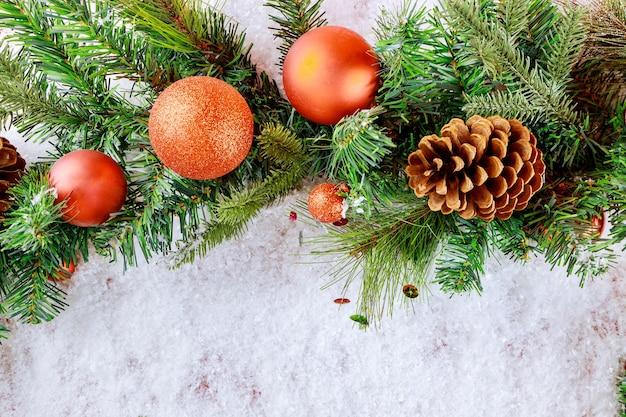 Świąteczna dekoracyjna piłka na świerkowej gałęzi na śniegu z czerwoną przestrzenią kopii