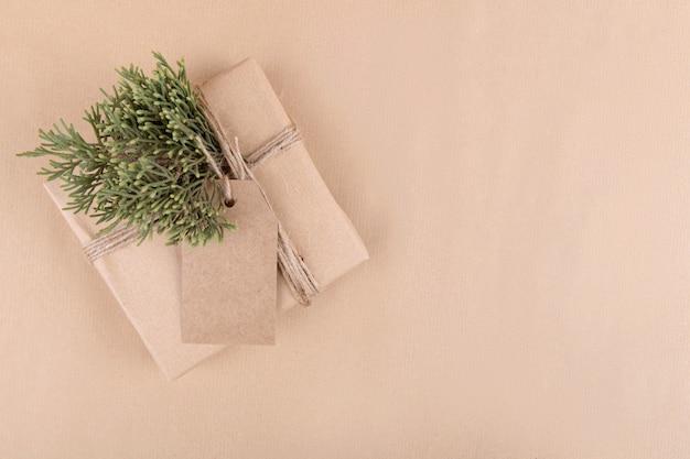 Świąteczna etykieta prezentowa makieta z pudełkiem owiniętym w papier z recyklingu rzemieślniczego z liną na tle papieru rzemieślniczego