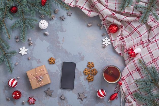 Świąteczna filiżanka do herbaty z cynamonem, ciastkami, gałązkami jodły, zabawkami, prezentami, smartfonem, kratą