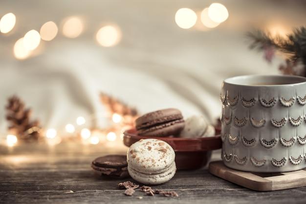 Świąteczna filiżanka i deser z makaronika na drewnie ze światłami i świątecznym wystrojem. przytulność i wygoda w domu