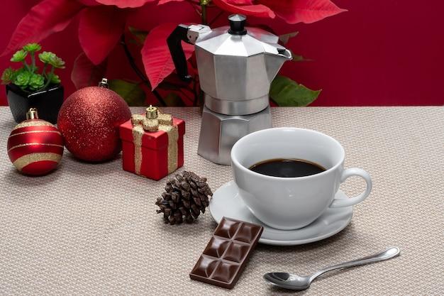 Świąteczna filiżanka kawy i tabliczka czekolady na beżowym ręczniku ze świąteczną dekoracją na czerwono