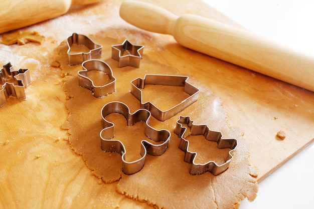 Świąteczna foremka do piernika na cieście z wałkiem do ciasta, pełna rama. świąteczne jedzenie, proces gotowania, rodzinna tradycja kulinarna, tradycja świąteczna i noworoczna.