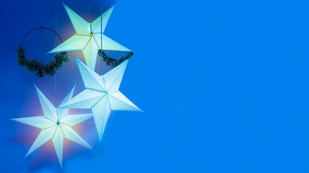 Świąteczna girlanda w formie gwiazdy z wieńcami, na boże narodzenie, nowy rok, wakacje na niebieskim tle. wystrój domu. copyspace