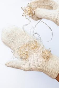 Świąteczna girlanda w rękach ubranych w dziane białe rękawiczki