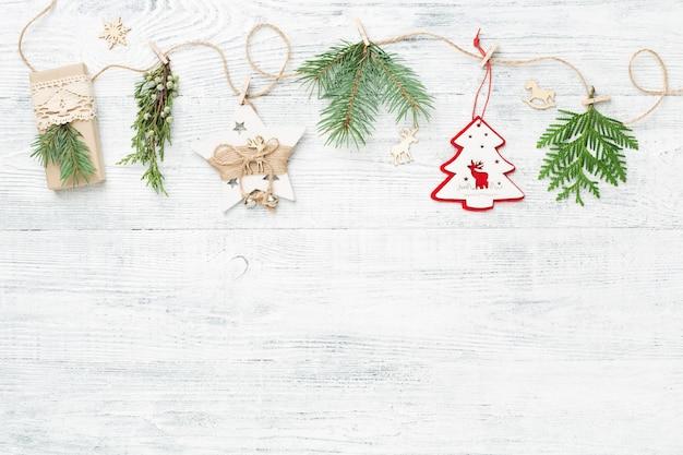 Świąteczna girlanda z gałęzi drzew iglastych i ozdób choinkowych na białym tle.