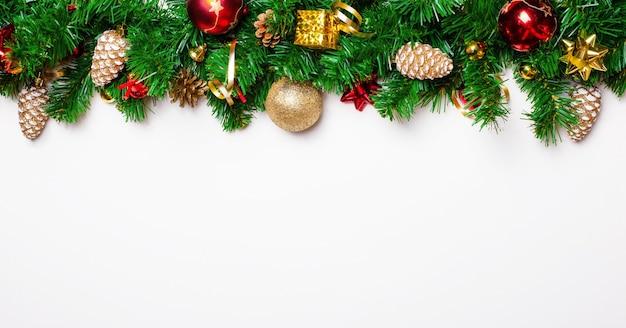 Świąteczna girlanda z gałęzi jodłowych, szyszek, kulek i prezentów. bombka na białym tle. koncepcja bożego narodzenia. skopiuj miejsce