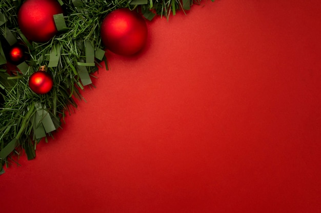 Świąteczna girlanda z liści i kulek na czerwonym stole