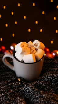 Świąteczna gorąca czekolada z piankami marshmallow z lekkim bokeh. selektywne ustawianie ostrości - zdjęcie pionowe