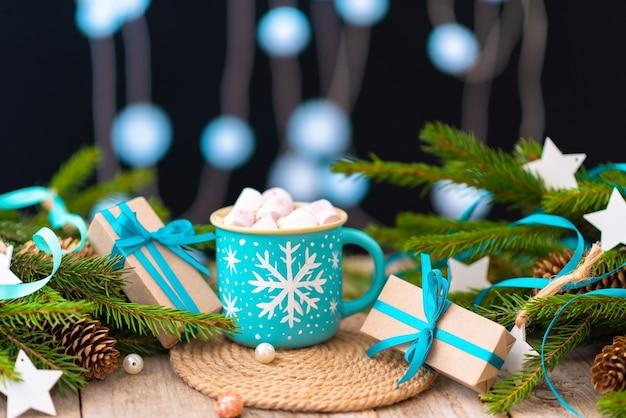 Świąteczna gorąca czekolada z plastrami ptasie mleczko. na tle iglastych gałęzi.