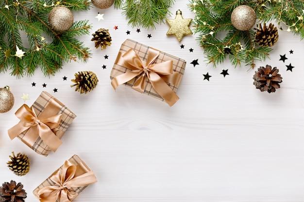 Świąteczna granica z gałązkami jodły, pudełkami na prezenty, złotym wystrojem i drewnianymi ozdobami