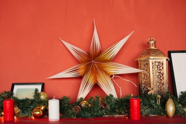 Świąteczna gwiazda dekoracyjna w wystroju pokoju na czerwonej ścianie