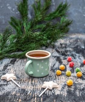 Świąteczna herbata w turkusowym kubku z białym groszkiem i słodyczami kulki żelkowe z białej czekolady i lizak